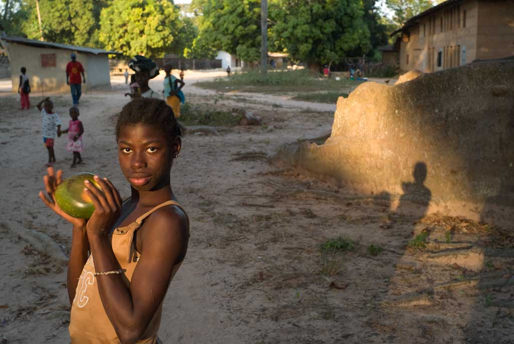 A girl holds a coconut as she poses in the village of Mlomp near Ziguinchor, Casamance, Senegal November 2008. © Francois Lenoir